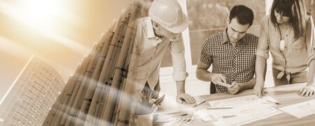 Architects working on plans at office; multiple exposure