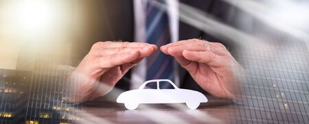 Concept of car insurance with hands over a car; multiple exposure
