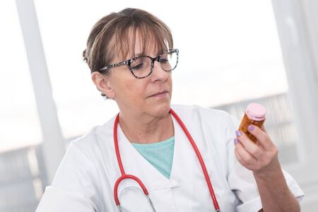 Female doctor looking at a bottle of pills in medical office