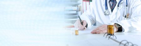 Doctor writing prescription at medical office; panoramic banner