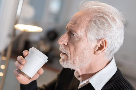 Thoughtful senior man holding a paper coffee cup