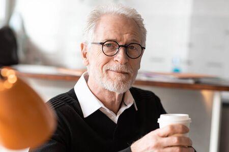 Senior businessman having a coffee break at office 写真素材