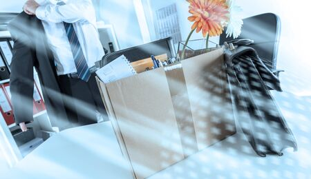 Businessman fired, leaving his office with his personal effects; multiple exposure Stock Photo