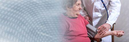 Doctor measuring blood pressure of senior woman; panoramic banner