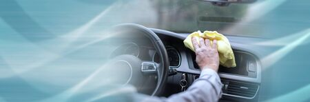 Man cleaning the dashboard of his car; panoramic banner Stock Photo