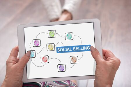 Social selling concept shown on a tablet held by a woman