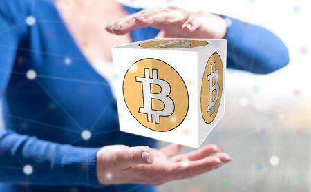 Bitcoin concept between hands of a woman in background Reklamní fotografie