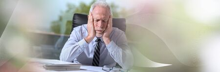 Stressed businessman sitting in office with head in hands; panoramic banner 版權商用圖片