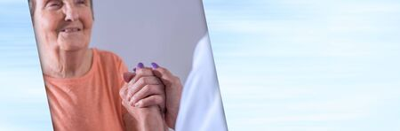 Hand of nurse holding hand of a senior woman; panoramic banner Imagens