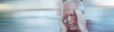 Mature man having a headache at home; panoramic banner