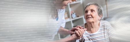 Nurse holding the hand of an old woman; panoramic banner Imagens