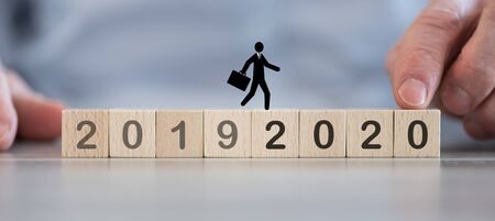 Businessman passing from 2019 to 2020 on wooden cubes