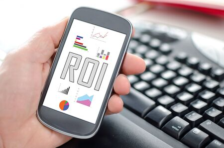 Hand holding a smartphone showing a roi concept
