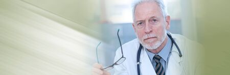 Portrait of male senior doctor looking the camera; panoramic banner Imagens
