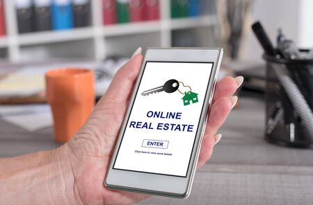 Female hand holding a smartphone with online real estate concept