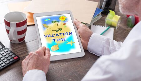 Vacation time concept shown on a tablet held by a man