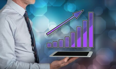Financial growth concept above a tablet held by a man Stock Photo