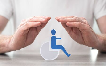 Disabled person protected by hands - Concept of disability insurance