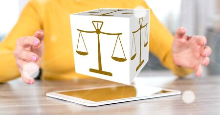 Digital tablet with justice concept between hands of a woman in background