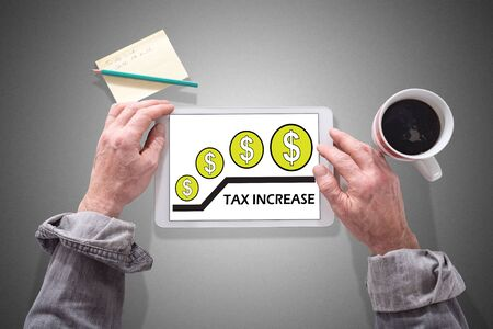 Male hands using a tablet showing tax increase concept Stok Fotoğraf - 129487893