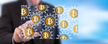 Man touching a bitcoin concept on a touch screen with his finger Stockfoto
