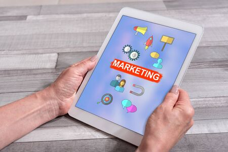 Female hands holding a tablet with marketing concept