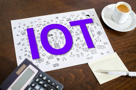 Iot concept on a paper placed on a desk
