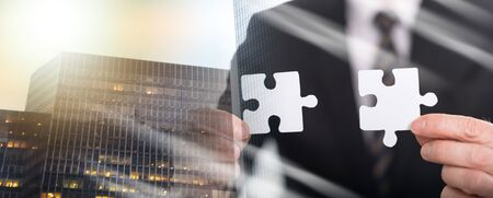 Hands joining two puzzle pieces, teamwork concept; multiple exposure Stok Fotoğraf