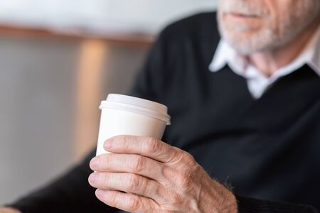 Businessman holding a paper coffee cup during break