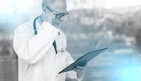 Senior doctor standing and reading notes on clipboard; multiple exposure Stok Fotoğraf