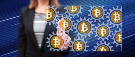 Woman touching a bitcoin concept on a touch screen with her fingers Stok Fotoğraf