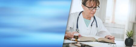Female doctor reading a textbook in medical office; panoramic banner