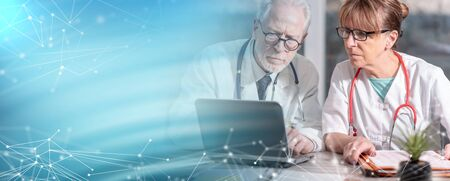 Two mature doctors discussing about medical report on laptop; multiple exposure