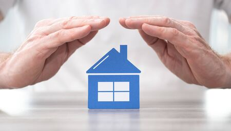 House protected by hands - Concept of home insurance Stok Fotoğraf