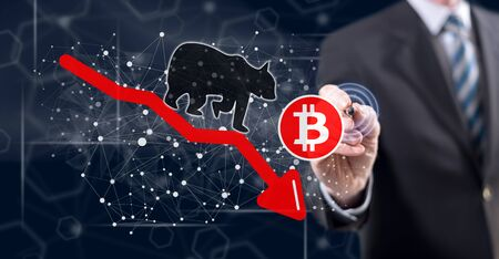 Man touching a bitcoin bearish trend concept on a touch screen with a stylus pen Stok Fotoğraf - 129487380