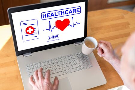 Man using a laptop with online healthcare concept on the screen Stok Fotoğraf