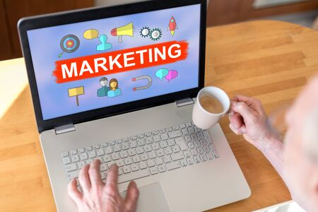 Man using a laptop with marketing concept on the screen Stok Fotoğraf