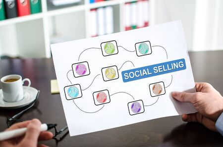Hand holding a paper showing social selling concept