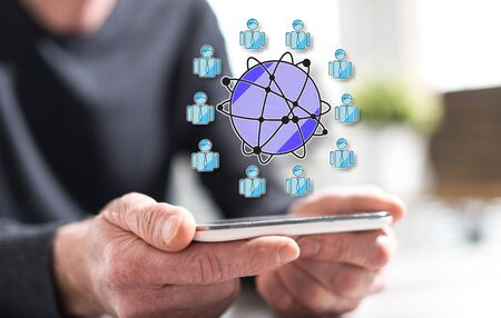 Hands of man holding a smartphone with global business concept Stockfoto