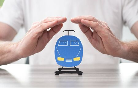 Train protected by hands - Concept of travel insurance
