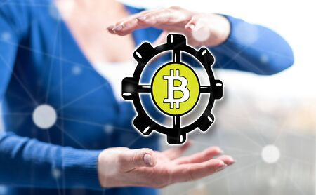 Bitcoin development concept between hands of a woman in background Stockfoto