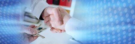 Realtor shaking hands with his client by delivering the keys, closeup; panoramic banner