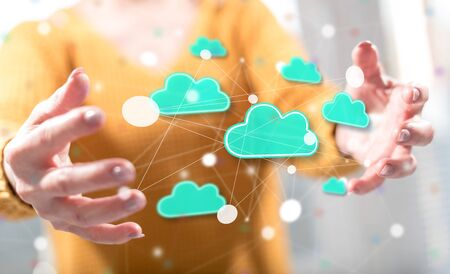 Cloud networking concept between hands of a woman in background