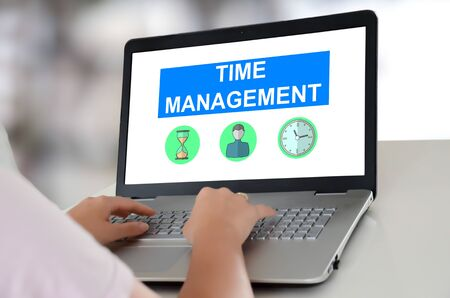 Woman using a laptop with time management concept on the screen