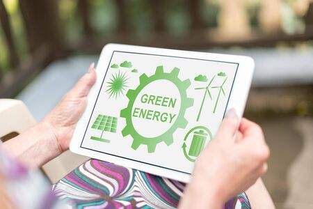 Green energy concept shown on a tablet held by a woman