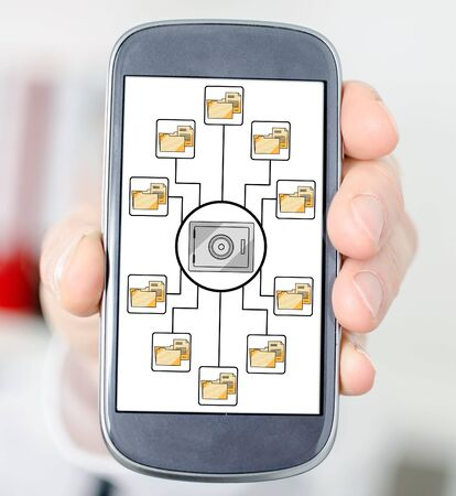 Hand holding a smartphone with data security concept