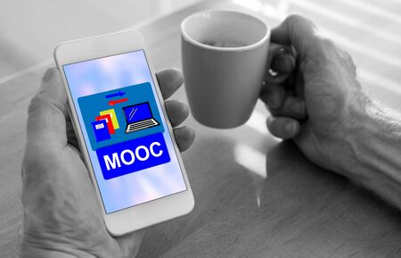 Male hands holding a smartphone with mooc concept and a cup of coffee
