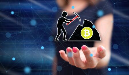 Bitcoin mining concept above the hand of a woman in background