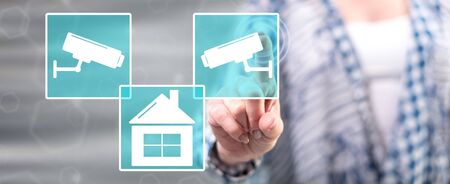 Woman touching a security camera concept on a touch screen with her finger Stock Photo