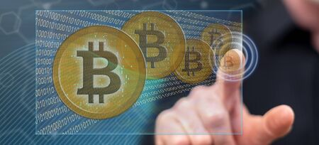 Man touching a bitcoin currency concept on a touch screen with his finger 写真素材